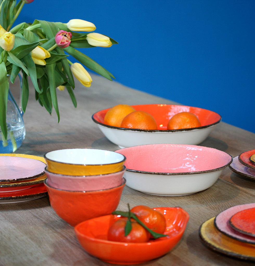 orange coloured papaya shaped serving dish with coloured tableware in yellow, pink and orange