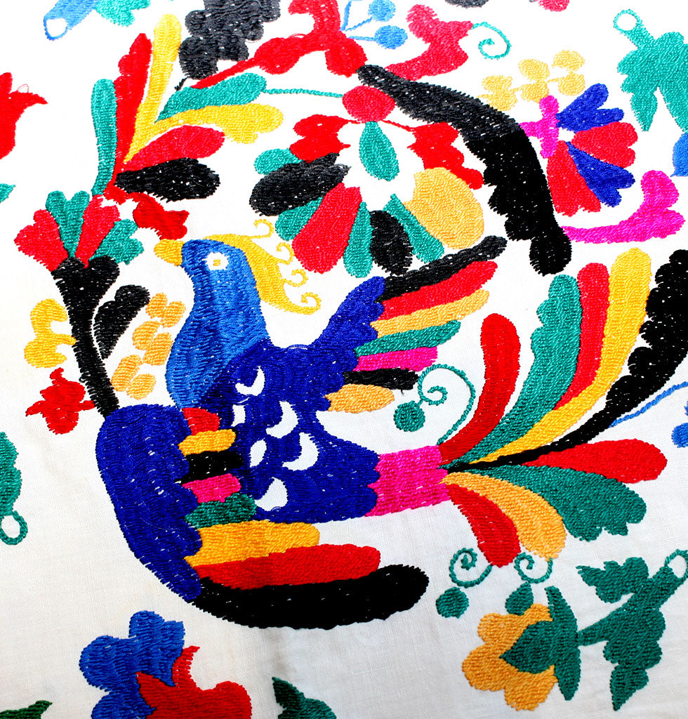 Vintage suzanis from the late Soviet era 1970-1980 featuring embroidered flowers and a blue folk art bird. Decorated by hand in purple and red flowers surrounded by Uzbekistan writing. Politcal Soviet traditional vintage embroidered wall hanging