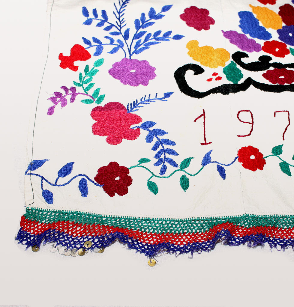 Detail of hand stitching. Vintage suzanis from the late Soviet era 1970-1980 featuring embroidered flowers and a folk art bird. Decorated by hand in purple and red flowers