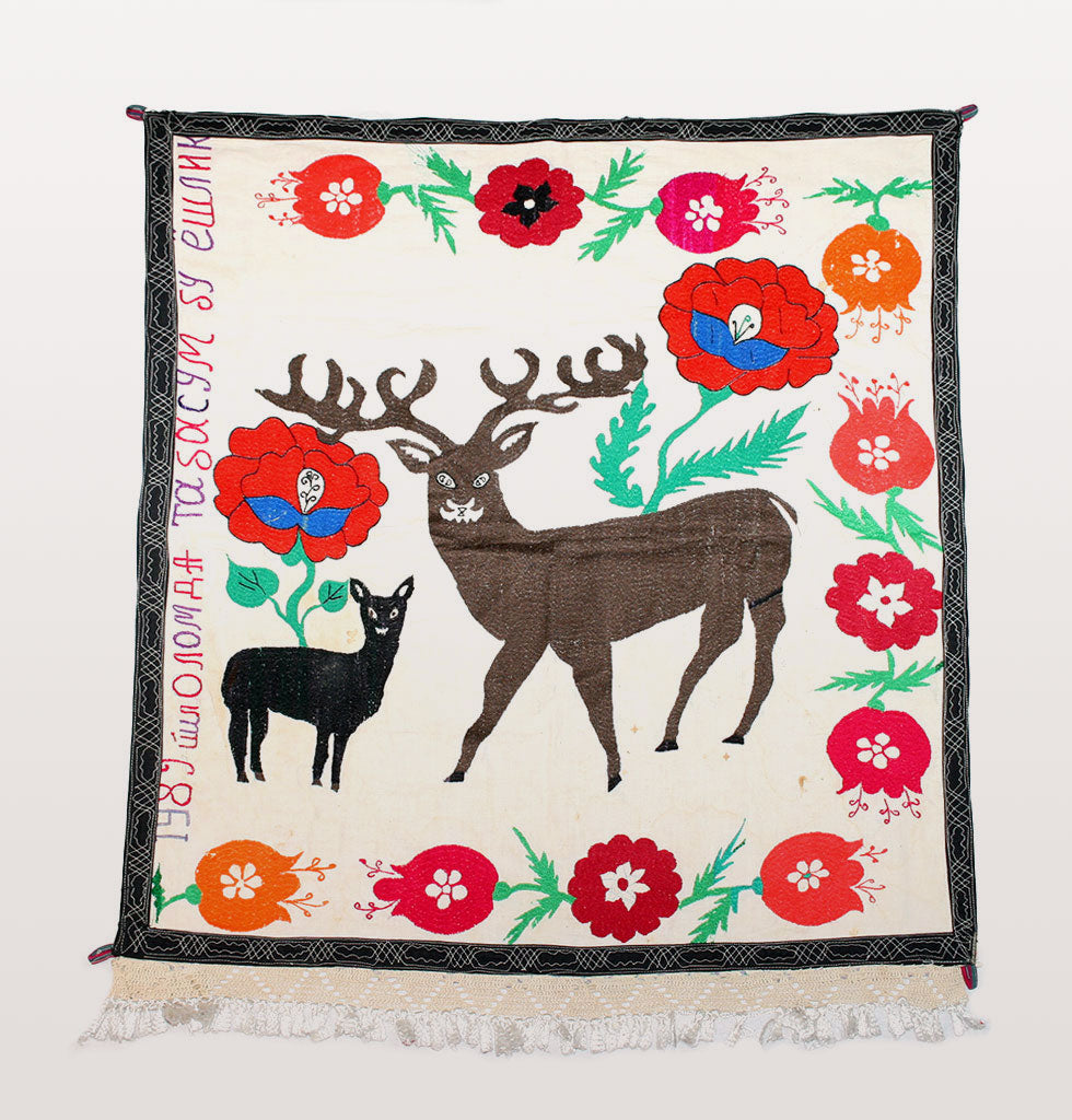 Vintage soviet era suzani wall hanging featuring two deer. Hand embroidered featuring bright red flowers and the date 1989 with Uzbekistan writing. Black border with white tassels and hanging loops. One off original hand stitched piece on white cotton
