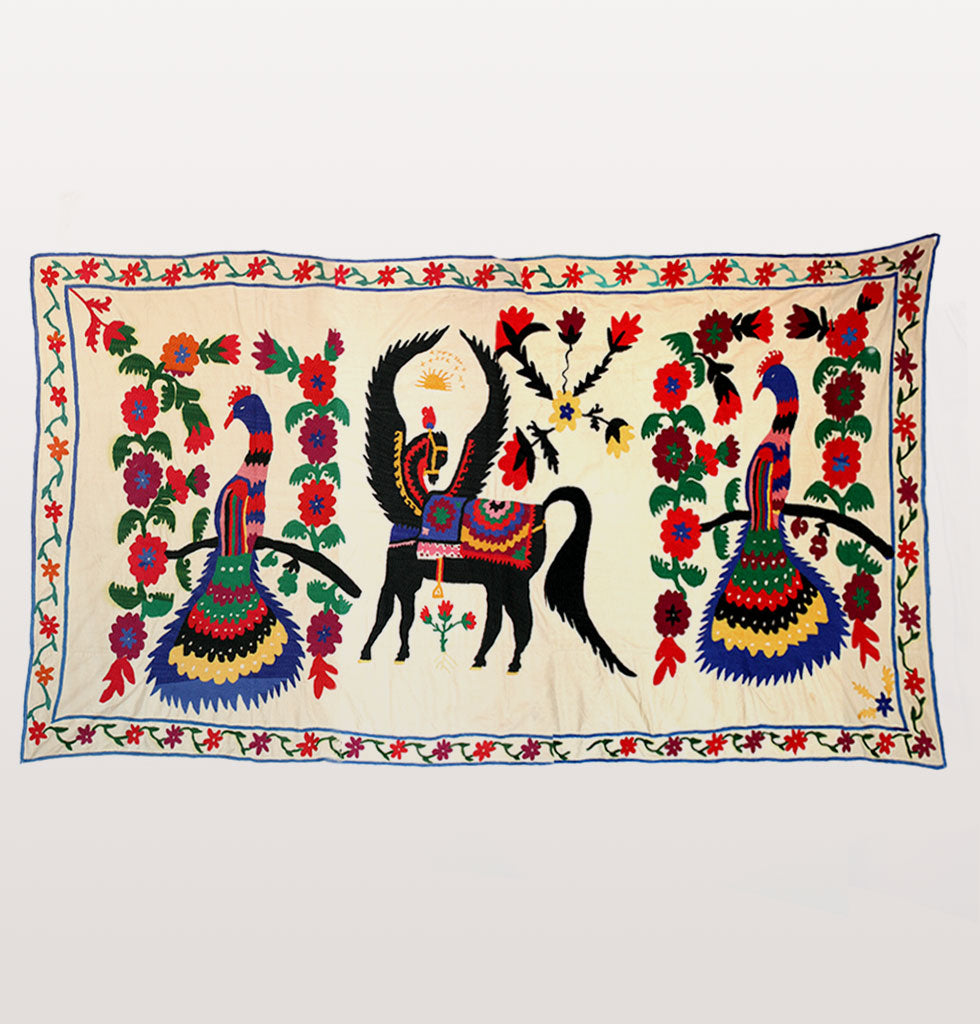 Large hand embroidered wall tapestry. Featuring brightly coloured peacocks and spiritual Pegasus this soviet era wall hanging originates from Uzbekistan. Featuring bright red folk art flowers this original vintage wall hanging is a stunning piece for your home. Use as a wall hanging on bed throw or cover for a eclectic aesthetic