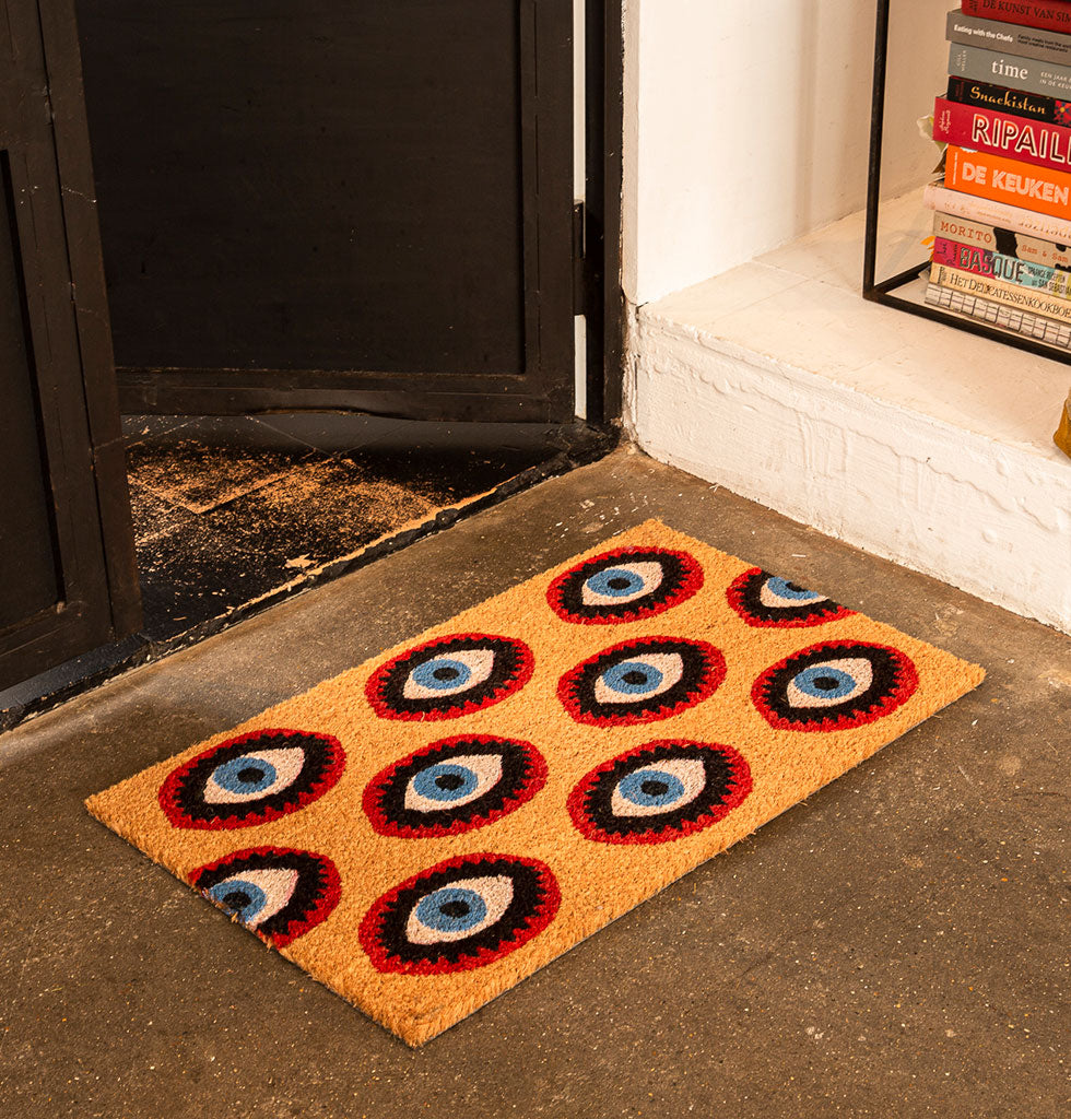 W.A.GREEN | KITSCH KITCHEN | EYE EYE! You'll feel instantly at home with this cheeky doormat. The eyes offer protection for your home as well as deep spiritual enlightenment.  Bold and modern design you'll enjoy coming home to.  Thick coconut fibre mat in multi-coloured print design.