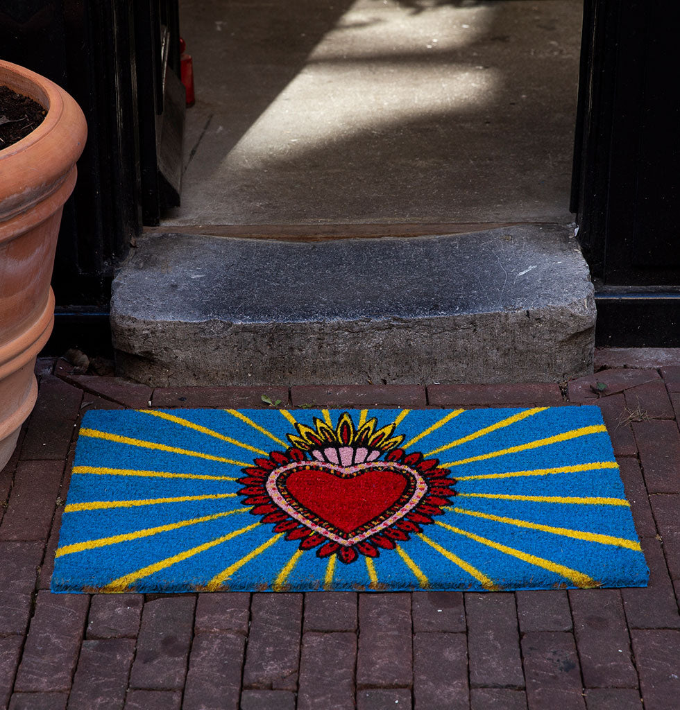 W.A.GREEN | KITSCH KITCHEN | BIENVENIDO! Home is where the heart is and nothing says welcome home more than this bright blue and yellow doormat. It's bold and striking design features a traditional Mexican milagros, a protective charm in the shape of a decorated heart.