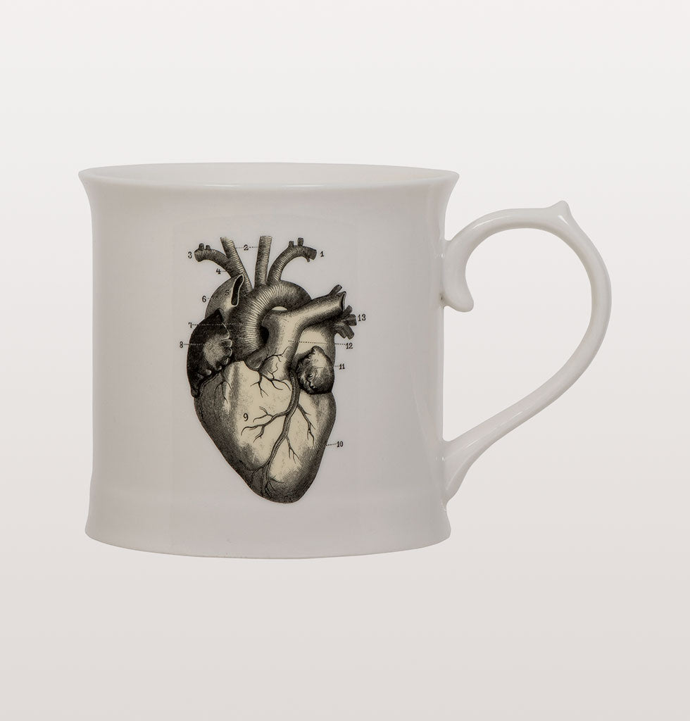 Give someone your heart. Looking like it's been lifted straight from a human anatomy book this simple coffee mug will make your heart go all of a flutter.  Designed by Magpie with in collaboration with the WelVegan white coffee mug is printed with a vintage black and yellow heart illustration.  Presented in smart illustrated gift box this would make a lovely gift to celebrate a china wedding anniversary or valentine. Size: L8cm H x Ø9CM  Material: Vegan fine china Care: