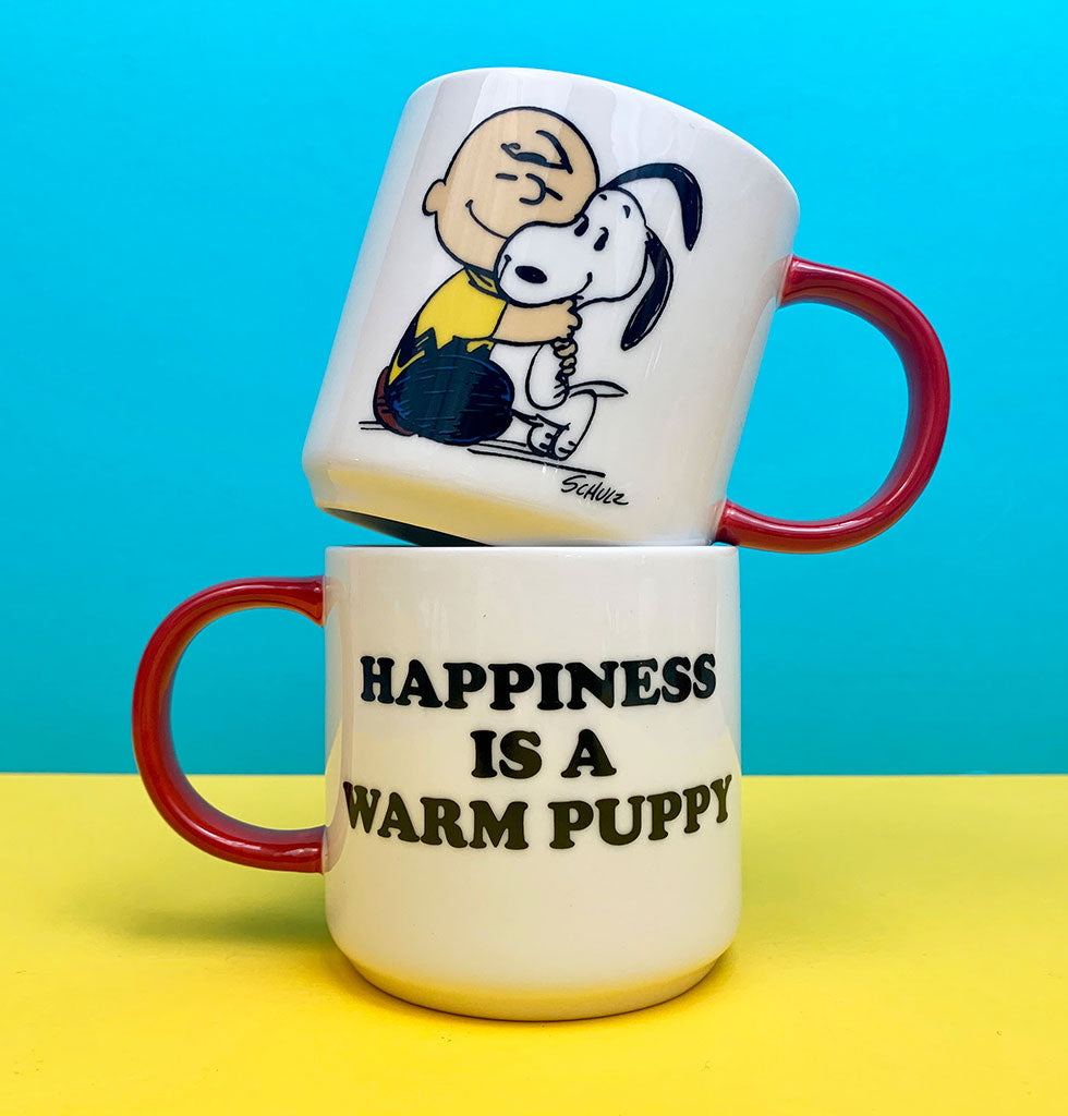 """Happiness is a warm puppy ""  Charlie Brown is giving us all the smiles with this cute mug featuring his best friend Snoopy.   This morning mug is great for making every cuppa feel cozy with a nostalgic scene from our favourite comic strip, Peanuts.  Presented in beautiful gift box by Magpie X Peanuts.  W.A.Green says ""Send a hug in a mug. This Snoopy cartoon coffee mug makes a fun gift for anyone you want to perk up in the morning""."