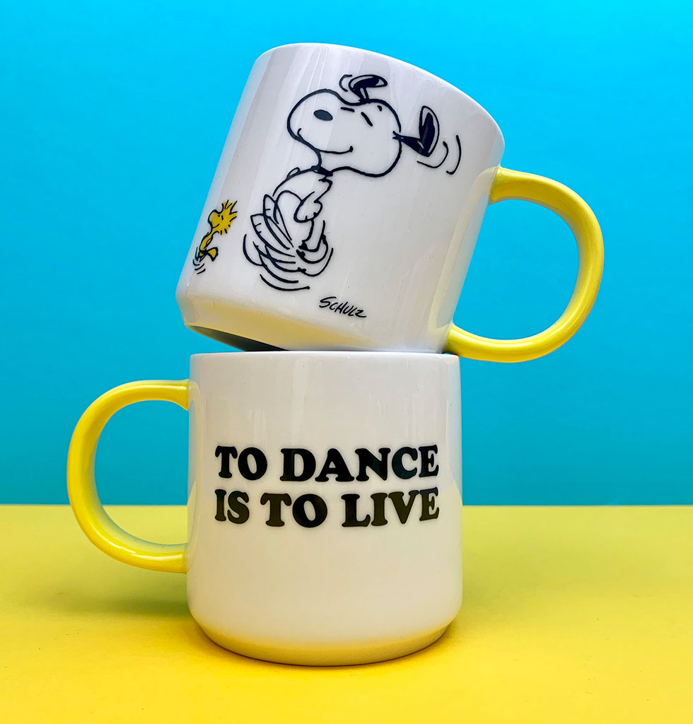 """To dance is to live ""  Snoopy's happy head says it all on this fun coffee mug guaranteed to wake you up with a smile in the morning.  Featuring everyone's favourite dog Snoopy and his sidekick Woodstock coming to the rescue with a morning brew from Charles M.Shultz's famous comic strip, Peanuts.  Presented in beautiful gift box by Magpie X Peanuts."