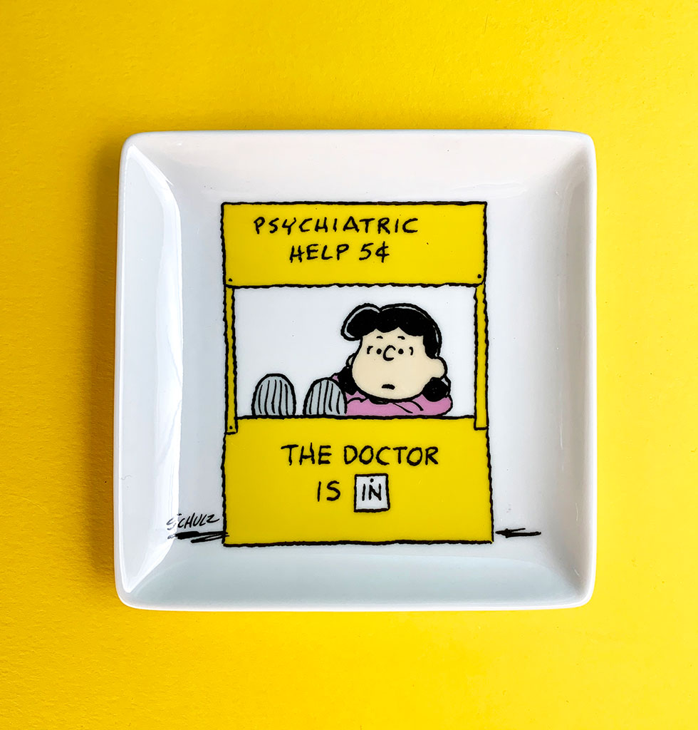 This sassy trinket tray really is the boss! Known for her crabby outbursts and sarcastic wit our favourite Lucy van Pelt from Peanuts is here dishing out lousy advise for a nickel from her psychiatry booth.    Featuring the iconic doctor's booth from the Peanuts cartoon strip this handy little trinket tray is perfect for keeping your jewellery, keys or other bits and bobs close to hand.   Presented in a beautiful gift box by Magpie X Peanuts.