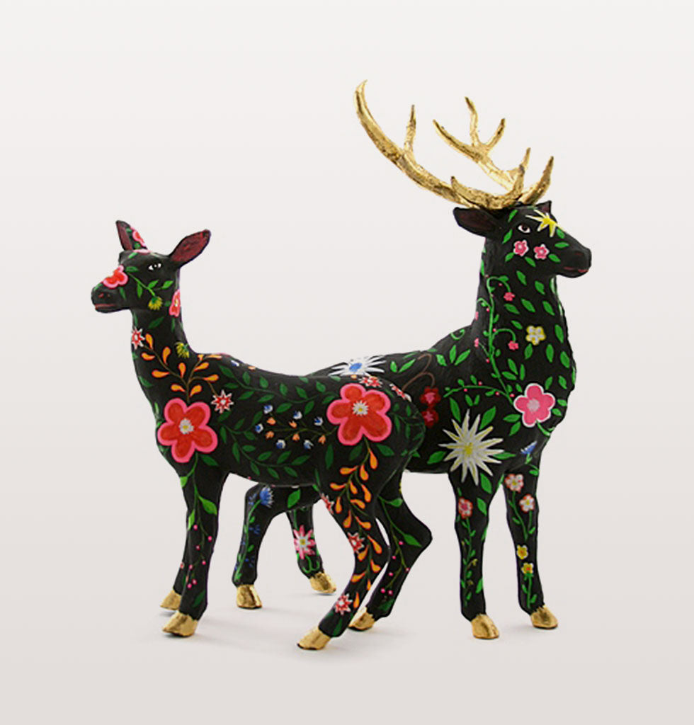 "Folk and florals are big news this Christmas and this charming couple are going to look magnificent on your mantlepiece.  The black stag and doe deer are painted with exquisite flowers and finished with gold on the hooves and majestic antlers.    Luxury floral Christmas reindeer set of two: Stag and Doe  W.A.Green says, ""Divine raindeers for your Christmas tablescape of dreams"