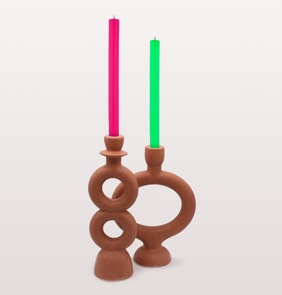 Terracotta candle holders by Madam Stoltz. Circles and Oval red brick coloured clay candle sticks with neon luxury dinner candles. wagreen.co.uk