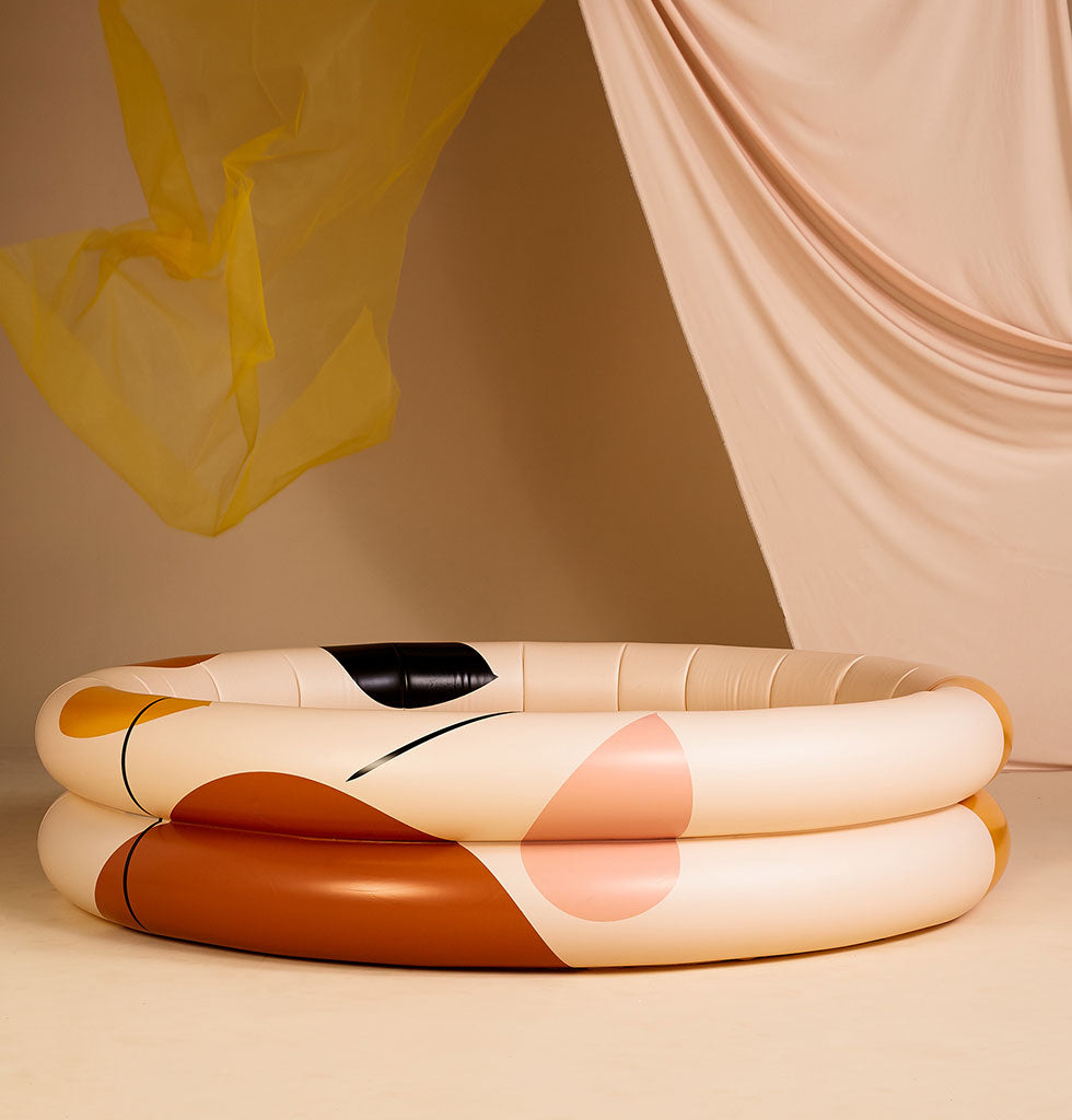 Shapes inflatable swimming pool by Mylle. Adult inflatable paddling pool in summer 2020 colours. Terracotta, pink, ochre and desert sand. Limited editionShapes pool by Mylle in a sunset palette of terracotta, ochre, sand and desert pink. £125 wagreen.co.uk