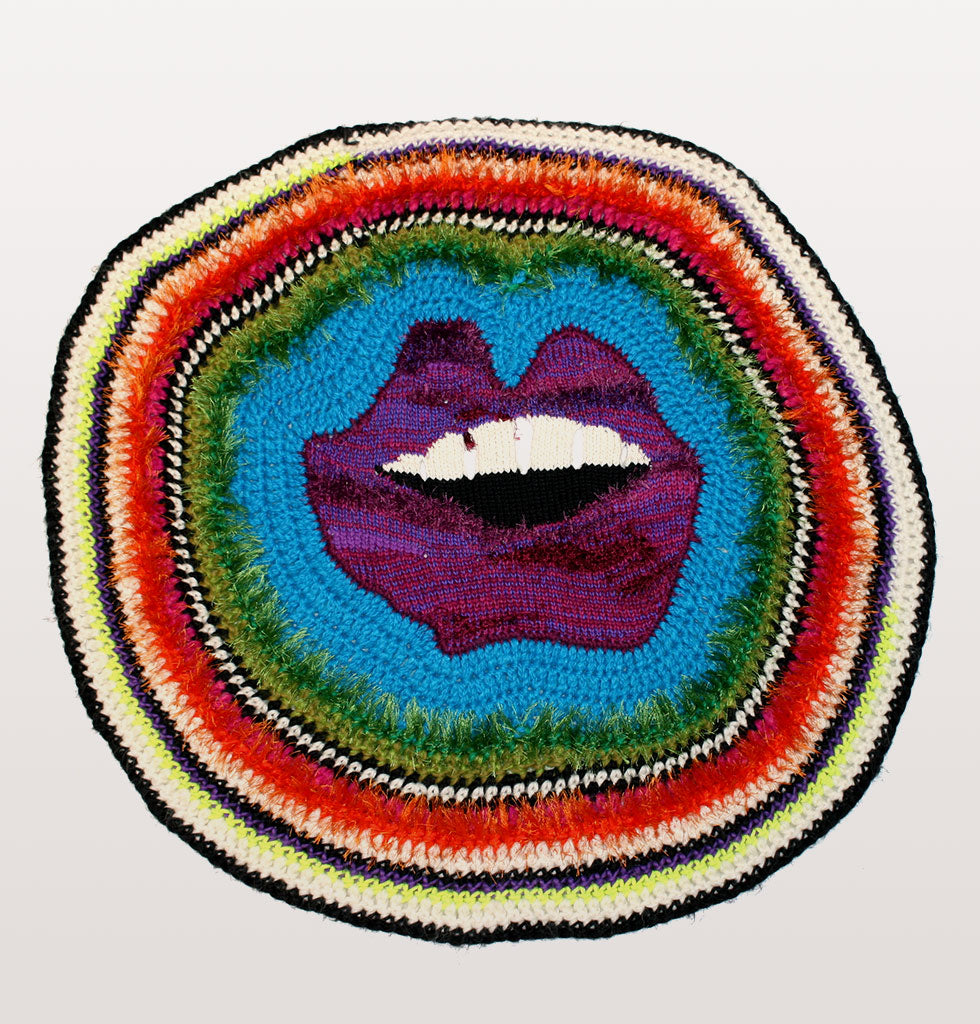 Jolly lips 2 by paris essex. Purple lips with teeth rainbow coloured round knitted wool blanket or wall hanging.