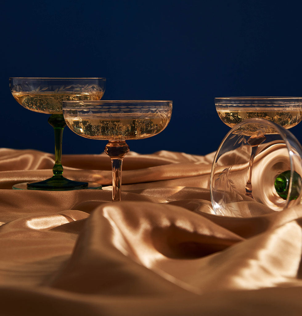 It's always the right time of day for Champagne. These beautiful Champagne coupe glasses with their stunning pale pink stems make every sip memorable.  The subtle leaf detail on the clear glass bowl is an unexpected touch which paired with the soft pink stem makes this Champagne coupe glass set something to be cherished.