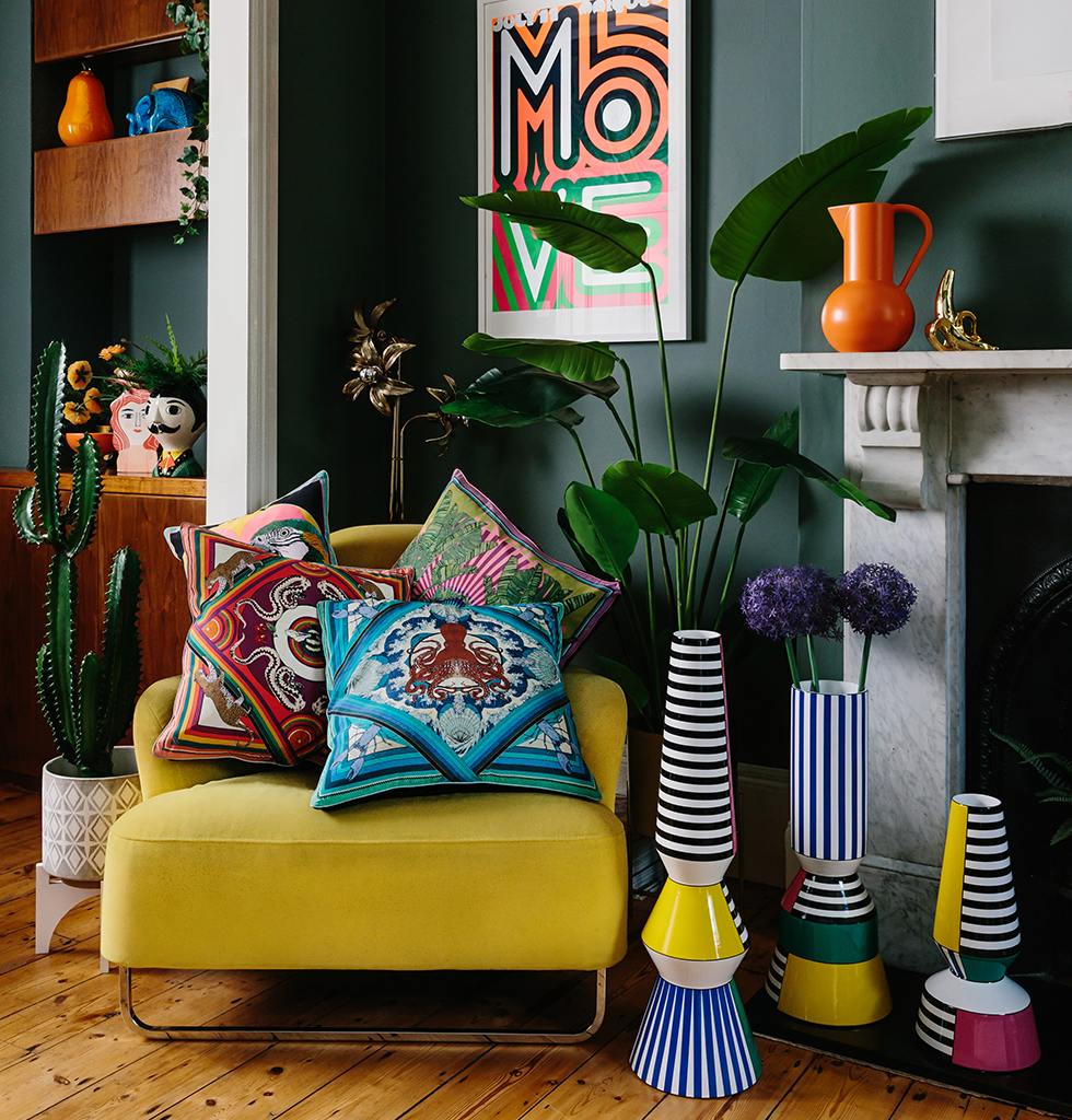 Maximalist home interior featuring yellow chair, silken favour cushions and large ceramic vases