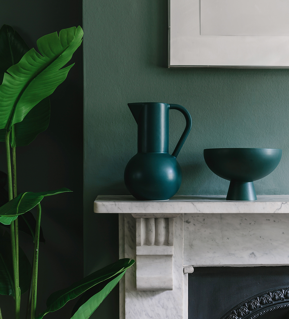 Large dark green ceramic Strom jug and bowl by Raawii on mantlepiece with dark green walls