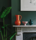 Coloured ceramics in dark green interior mantlepiece