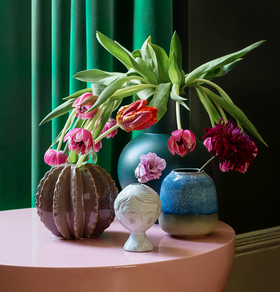 Pink and green interiors featuring dark green Raawii vase and Mila table by Pulpo
