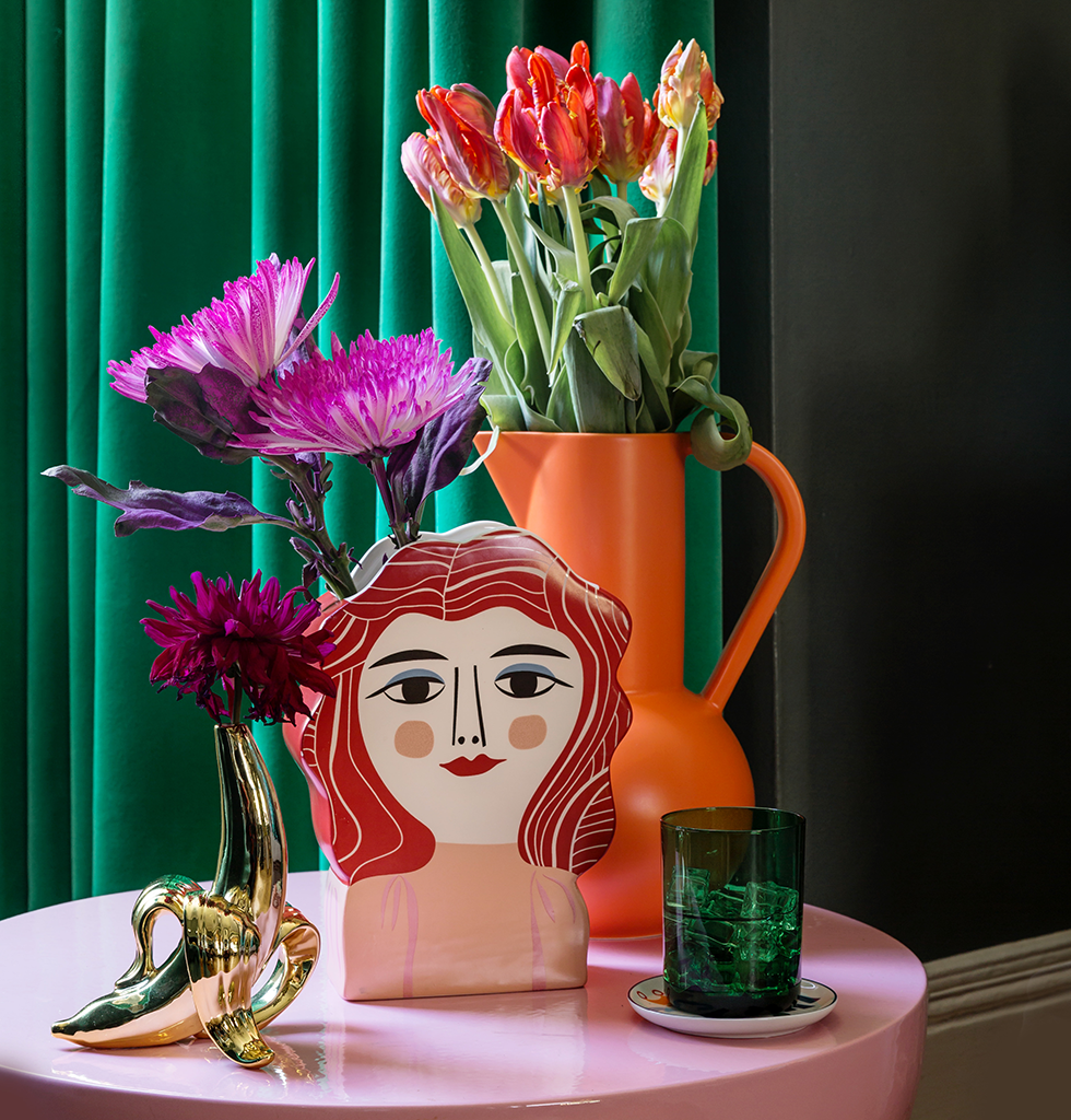Miss Meyer by Kitsch Kitchen vase with large orange ceramic jug by Raawii and gold Jonathan Adler banana stem vase on pink Mila Pulpo table. wagreen.co.uk