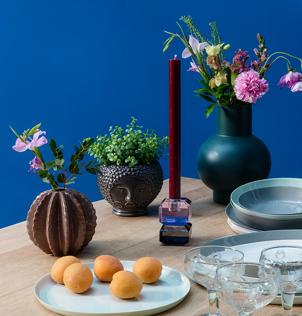 Table setting with bright blue walls and green ceramics
