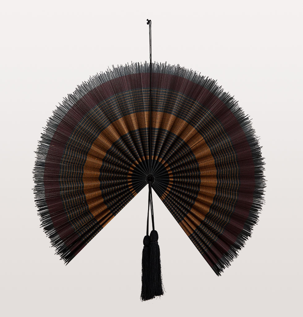 "Add an oriental-inspired touch of texture to your walls with this striking bamboo fan in rich luxurious colours of aubergine, mustard and black.   The impressive size makes for a grand impression in any room and is sure to be a conversation starter.   W.A.Green says: ""Really elegant natural design. Pair with darker rich tones for an atmospheric space""  Size : D:70cm"