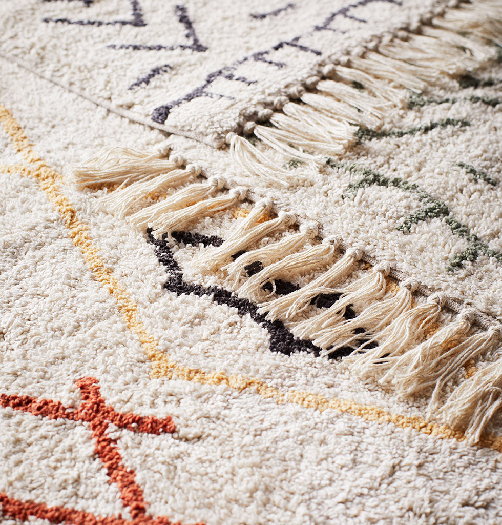 MADAM STOLTZ | BERBER BATH MAT MULTI | Step out of the shower and deep into the souk with a beautiful soft Berber inspired bath mat.  Super soft off white ivory coloured cotton is patterned with a multi coloured graphic black, terracotta orange and saffron yellow design. The large tasseled bath mat is lovely and thick with a clever slip proof latex backing.