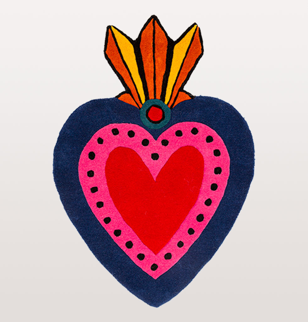 Bring the passion of Mexico into your home with this milagro inspired heart shaped rug.  Home is where the heart is and nothing says 'welcome home' more than this bright pink, red and navy rug in your room. It's bold design by Kitsch Kitchen features a traditional Mexican milagro design, a protective charm in the shape of a decorated heart.   Handmade in India as part of a community project using traditional rug making techniques.