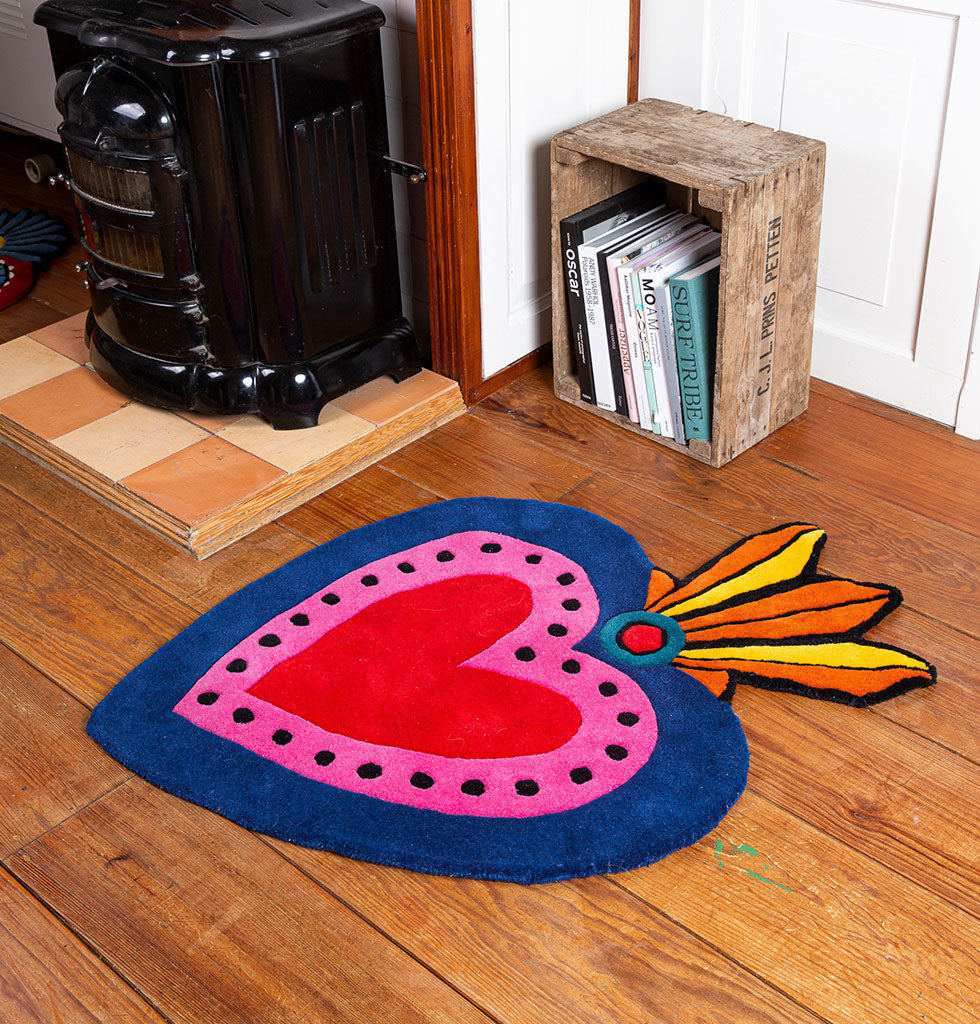 W.A.GREEN | KITSCH KITCHEN | Bring the passion of Mexico into your home with this milagro inspired heart shaped rug.  Home is where the heart is and nothing says 'welcome home' more than this bright pink, red and navy rug in your room. It's bold design by Kitsch Kitchen features a traditional Mexican milagro design, a protective charm in the shape of a decorated heart.   Handmade in India as part of a community project using traditional rug making techniques. £160 wagreen.co.uk