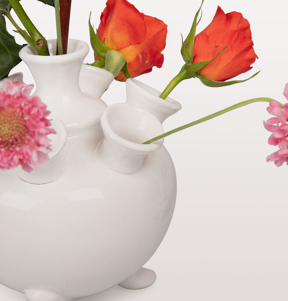 "A modern twist on the much famed traditional tulip vase which originated from The Netherlands back in the 1700s when tulips first became fashionable. 7 stem holes form part of this ornate table and centrepiece vase. This white tulip vase would look beautiful with an array of flower stems.  Presented in smart box for easy gifting.  W.A.Green says, ""This simple white 7 stem hole vase captures the purity and rural spirit of the cottagecore aesthetic which is big news in homes right now""."