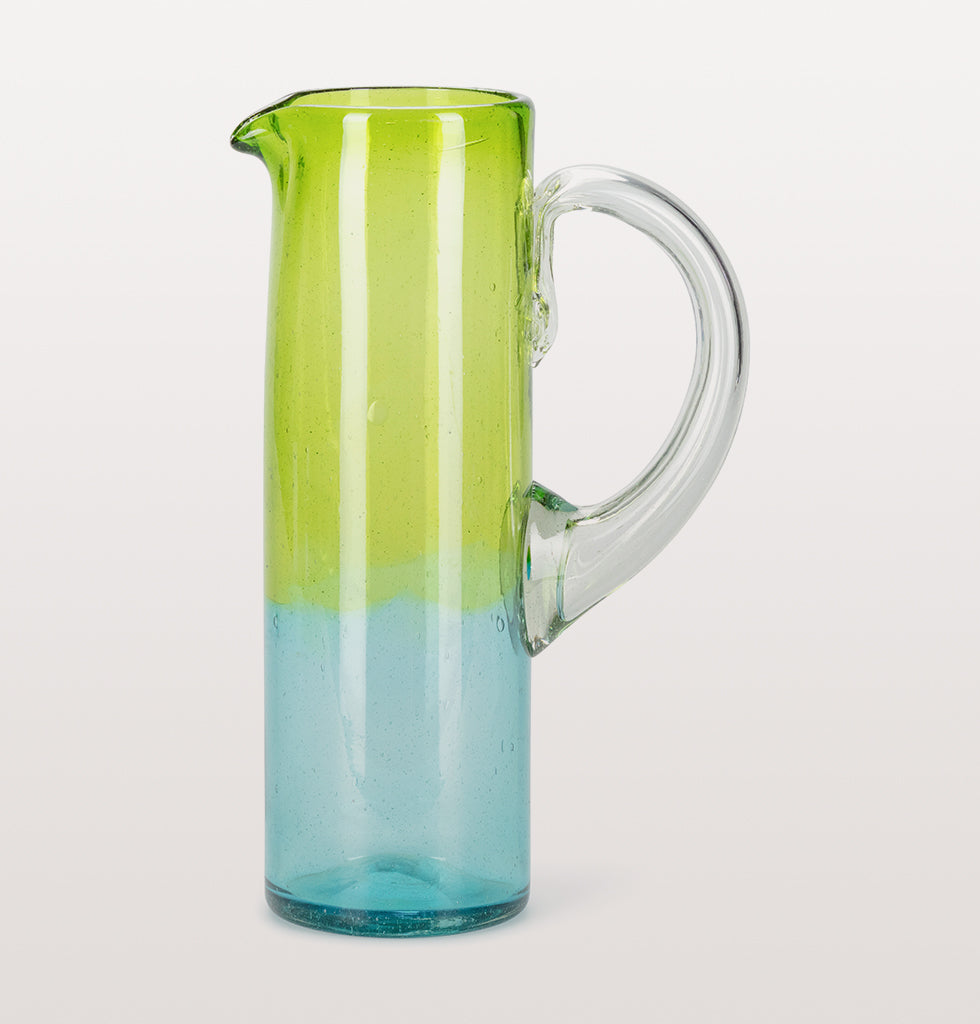"Zesty and fun ombre glass jug from Mexico. Hand made using traditional glass making techniques using recycled glass this straight sided glass jug is strong and stylish. The lime green glass fades into a light turquoise blue making this simple piece super interesting.  W.A.Green says, ""A fun water jug with punch""."
