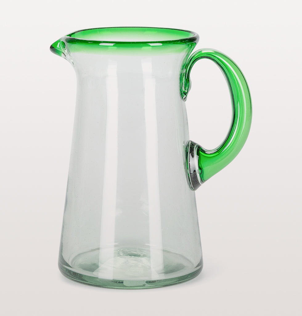 Clear recycled glass lechero jug from Mexico with green coloured rim and handle.  Hand made using traditional glass making techniques this fluted jug is strong and stylish. The bright green rim makes this a real head turner.