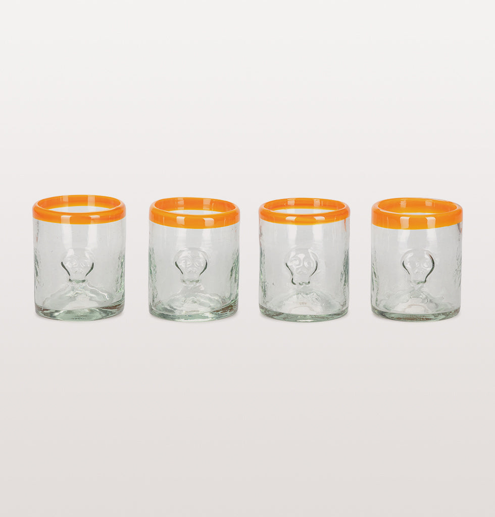 "Mexican glassware makes us feel happy. Make a simple drink feel substantial with these heavy recycled tumbler glasses. Featuring a simple straight sided design with orange rim and embossed sugar skull motif.   W.A.Green says, ""We'll be chinking glasses with everything from a simple lime squash to a cheeky Desperados beer""  Milagros x W.A.Green EXCLUSIVE  Set of 4 glasses"