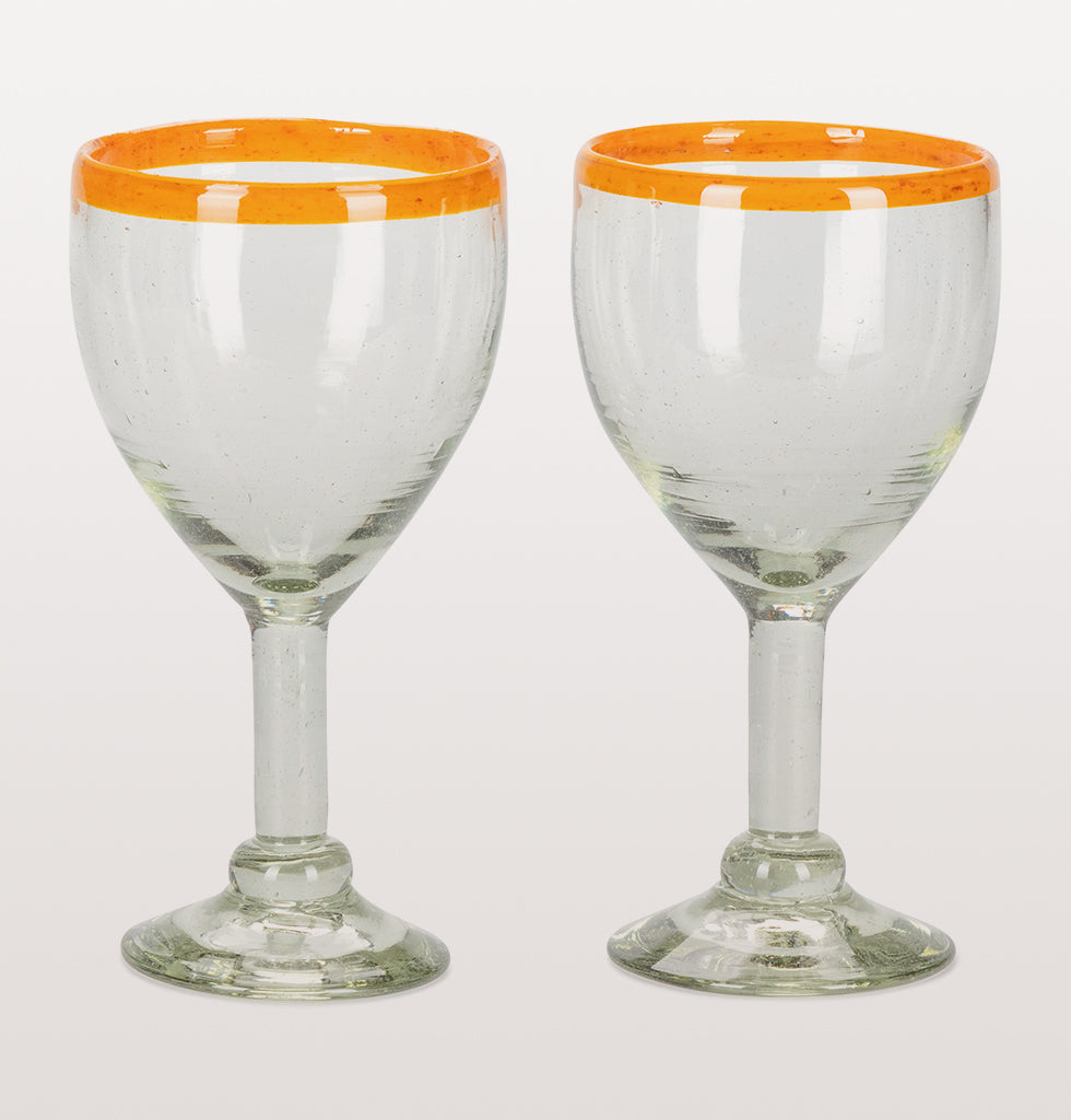 Arriba! Nothing says summer to us like Mexican glassware. These beautiful heavy wine glasses are decorated with a simple bright orange rim. These recycled handblown glasses are superb for making a simple drink feel like you've got the sand between your toes.   Set of two wine glasses.   These glasses are handmade, making no two exactly the same. The beauty is in the difference.