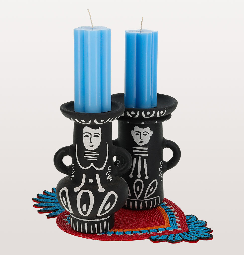 Folklorico Candle Set  Arriba! This black and white dancing duo are inspired by the traditional Mexican Day of the Dead celebrations. Dancing the baile folklorico from dust till dawn this perfect couple has been paired with our daisy blue pillar candles and hand beaded protective milagro display table mat.  Pedro and Ines Candle Holders Hand made Blue Daisy Pillar Candles Red and blue heart shaped milagro display coaster