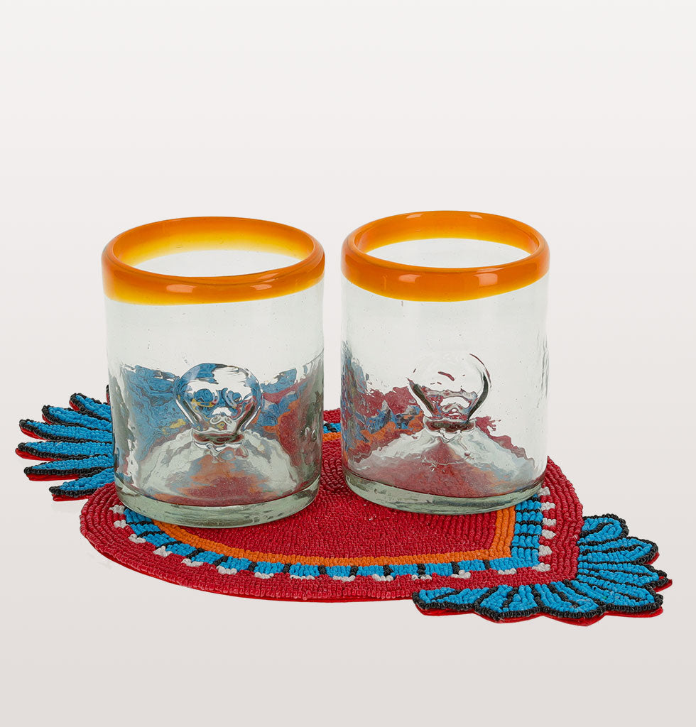 W.A.GREEN | KITSCH KITCHEN | Red milagro tablemat and set of 2 skull clear glasses with orange rim. wagreen.co.uk