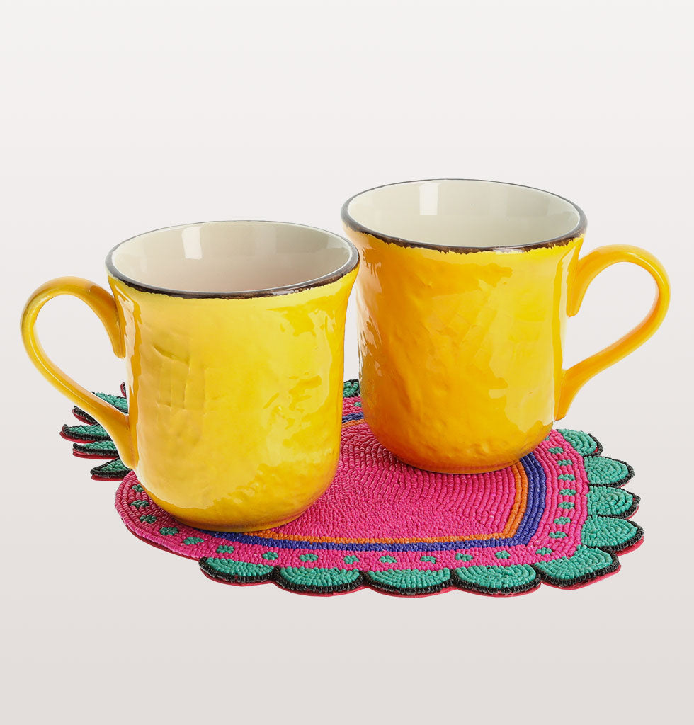 Hello Sunshine Mug Set  Say hello to some morning sunshine with this bright yellow mug set. Our sunshine yellow majolica mugs are the perfect size for a generous cup of tea and partnered with this hand beaded Mexican inspired milagro display mat they radiate joy and contentment.   Hand beaded milagro heart display coaster Two bright yellow ceramic mugs