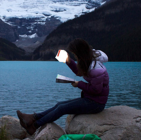 A Woman Using the LuminAID PackLite USB Solar Lantern in the Outdoors