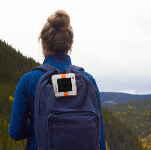 The LuminAID PackLite Solar Lantern Attached to a Camper's Backpack