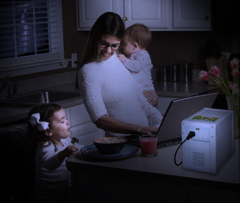 A mom powering her laptop with a kisae solar battery bank during a thunderstorm