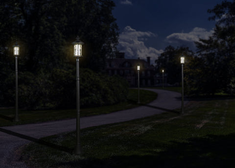 Classy Caps Black Aluminum Hampton Solar Lamps on posts illuminating a driveway path