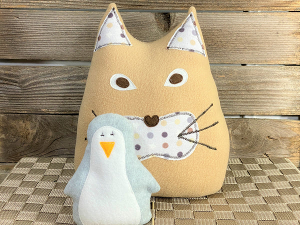 Beige cat pillow with brown and gray polka dot print and a gray penguin hot and cold pack