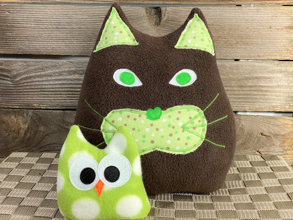 Brown cat pillow with green and brown dots and a green and white polka dot owl hot and cold pack