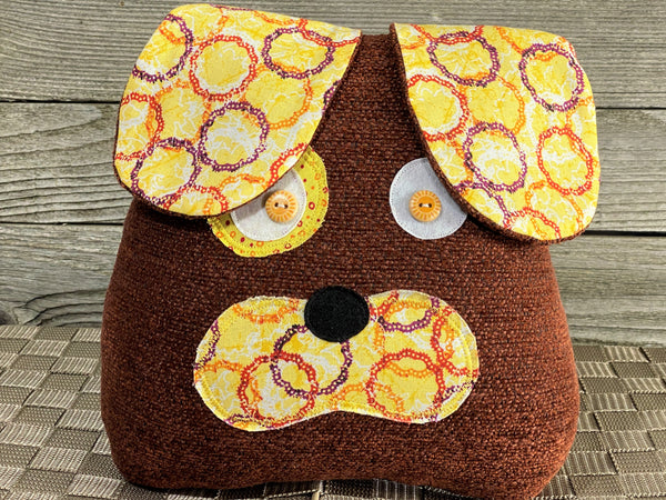 Floppy eared puppy shaped pillow in reds and yellows