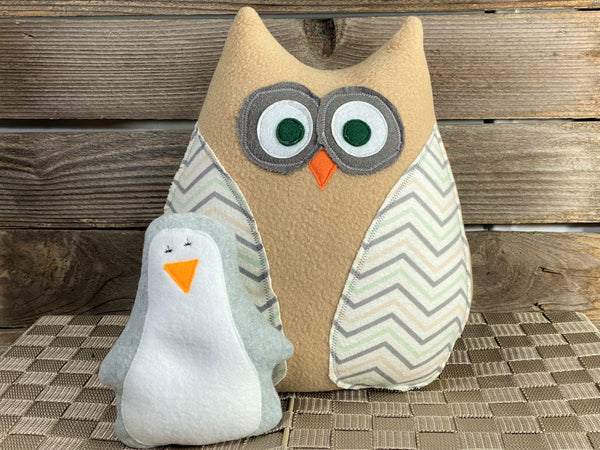 Beige owl pillow with chevron wings and a gray hot and cold penguin for boo boos