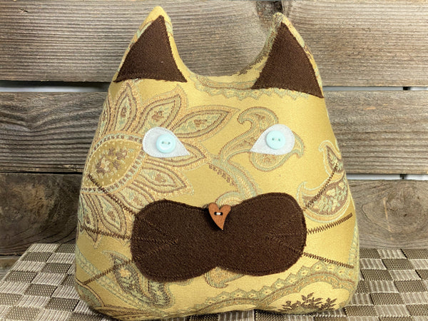 Beige satin cat shaped pillow with deep brown accents