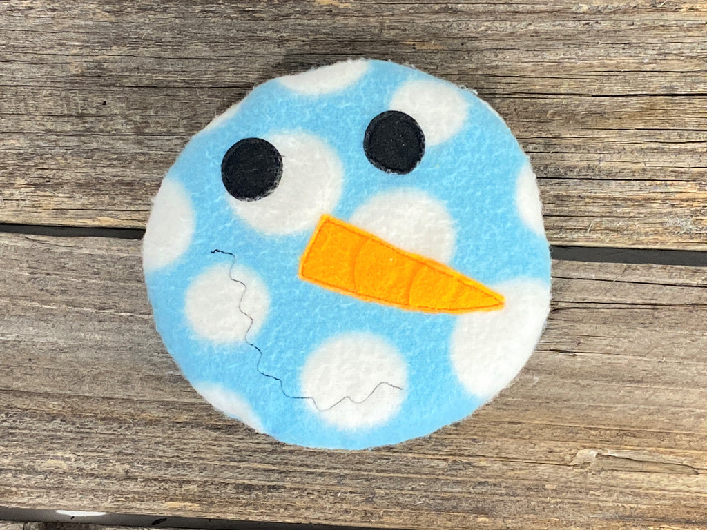 Blue and white dotted snowman face for use as a hot or cold pack