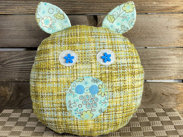 Green and teal boucle pig pillow with light blue accents