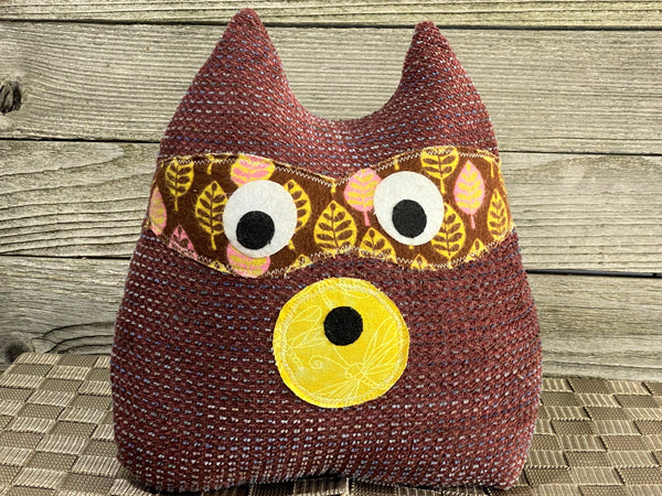 Brick red raccoon pillow with yellow accents