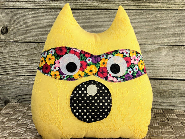 Yellow raccoon pillow with black and floral accents