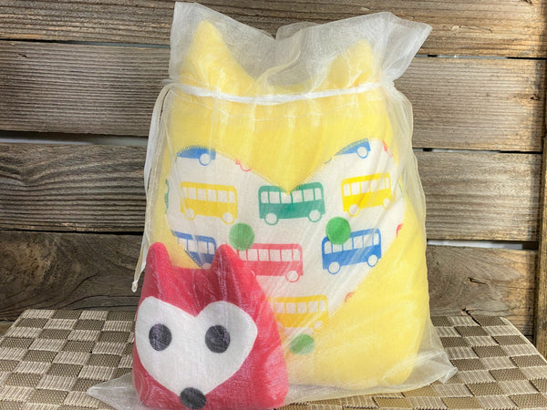 Yellow fox pillow with primary color buses and a red fox hot and cold pack in an organza bag