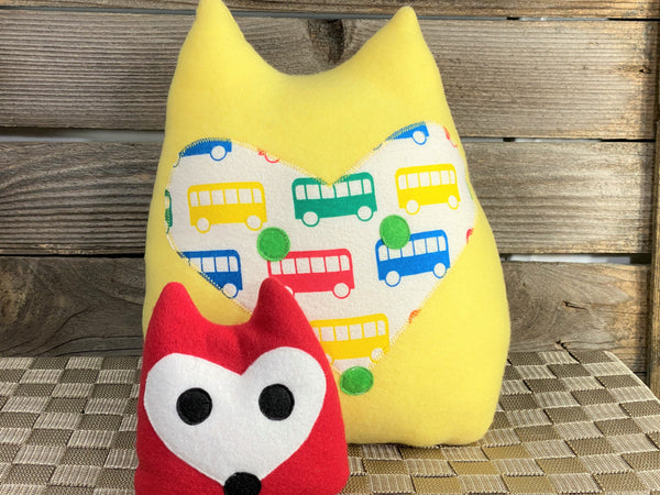 Yellow fox pillow with primary color buses and a red fox hot and cold pack
