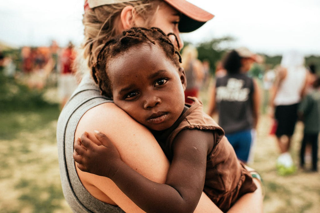 Blonde Woman Holding African Orphan